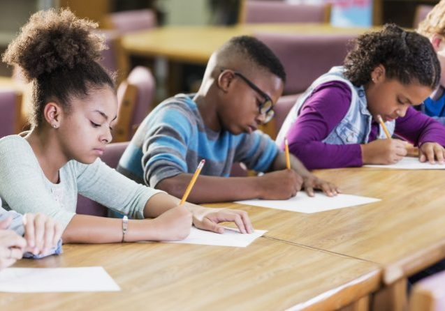 A group of five multi-ethnic elementary school students sitting in a row at a table, taking a test, writing with pencils on paper. They are 10 and 11 years old. The focus is on the African-American girl 2nd from the left.